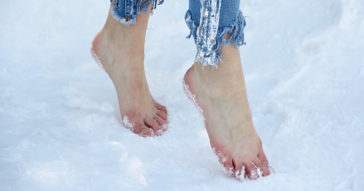 woman walking barefoot in the snow