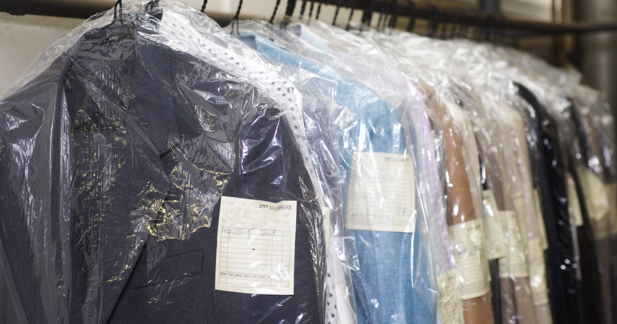 drycleaned blazers and other clothes hanging in plastic on clothing rack