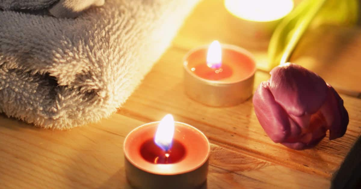 best ways to relax after a stressful day - image of towel, tealights, and a rose