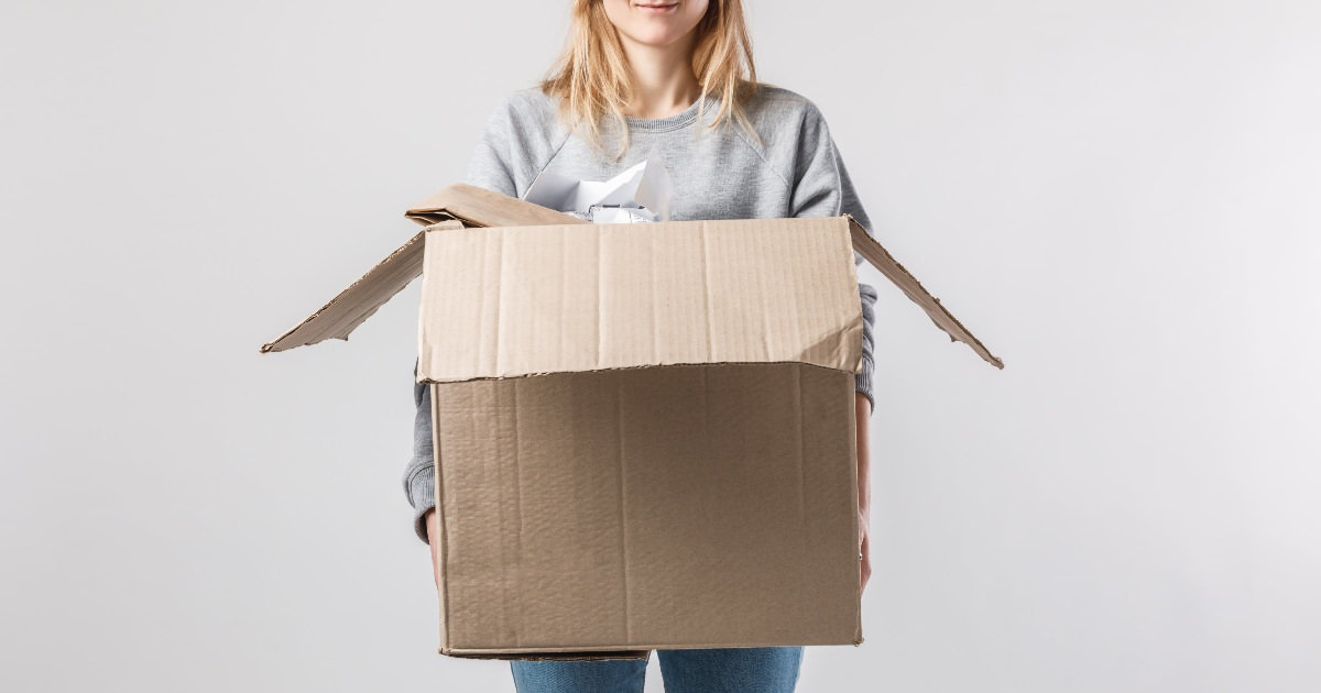 young professional woman holding a box of old work clothes to recycle, donate, or sell