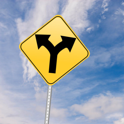 stock photo of yellow traffic sign showing one path with two arrows forking out