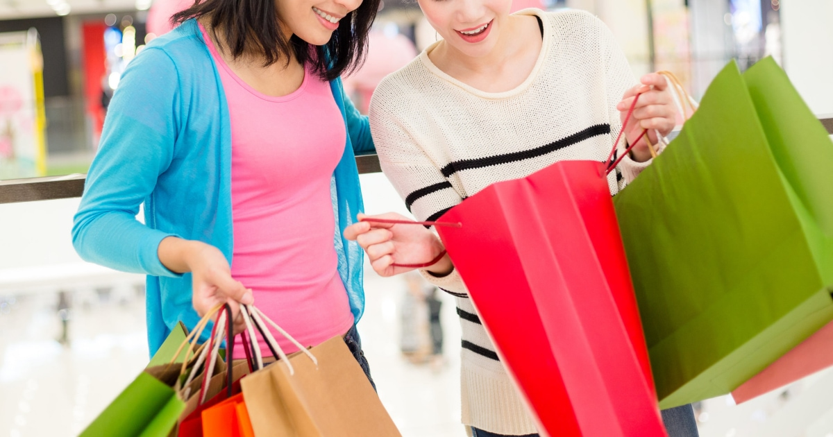 two professional young women look at each other's shopping bags