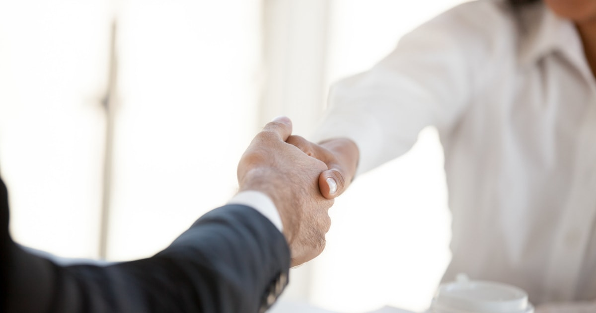 businesswoman and man in suit shaking hands
