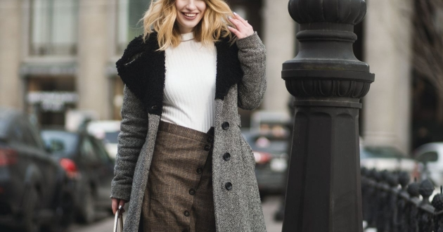 stylish young professional woman walking down a city street wearing a coat and sweater