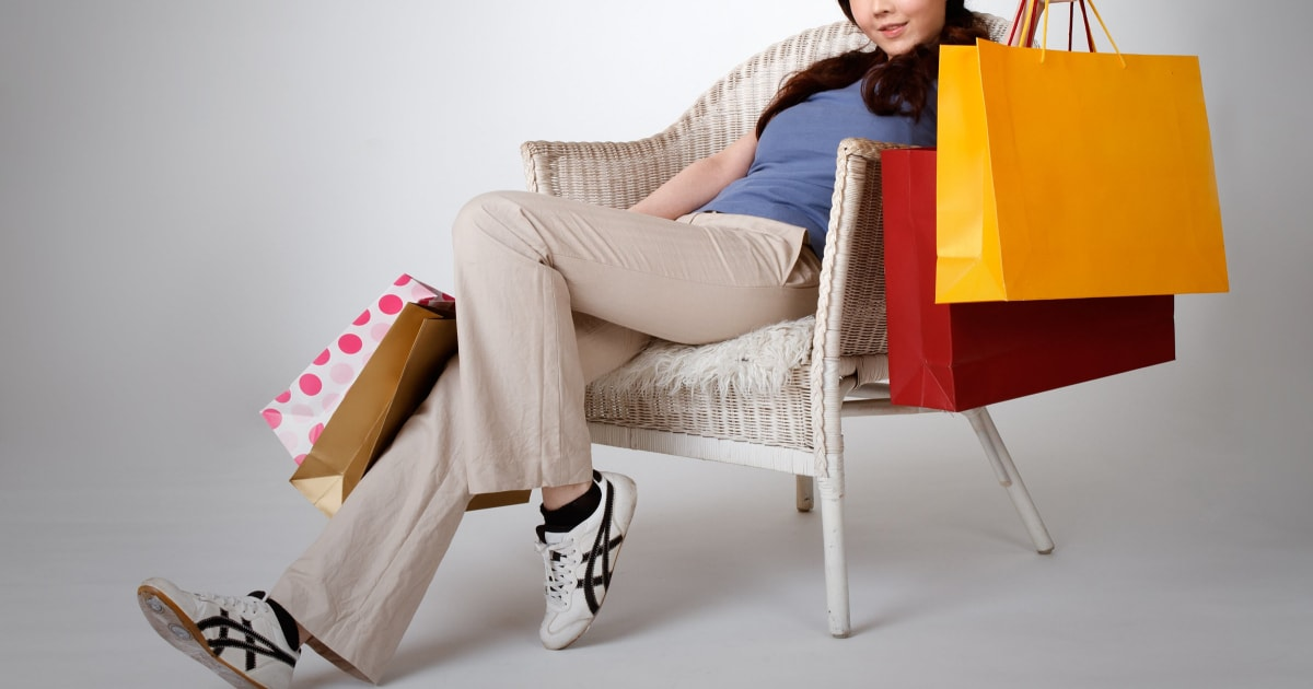 young professional woman lounging, surrounded by shopping bags