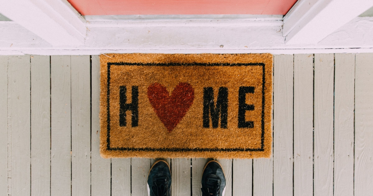 person in black sneakers standing in front of doormat that says HOME and a pink door