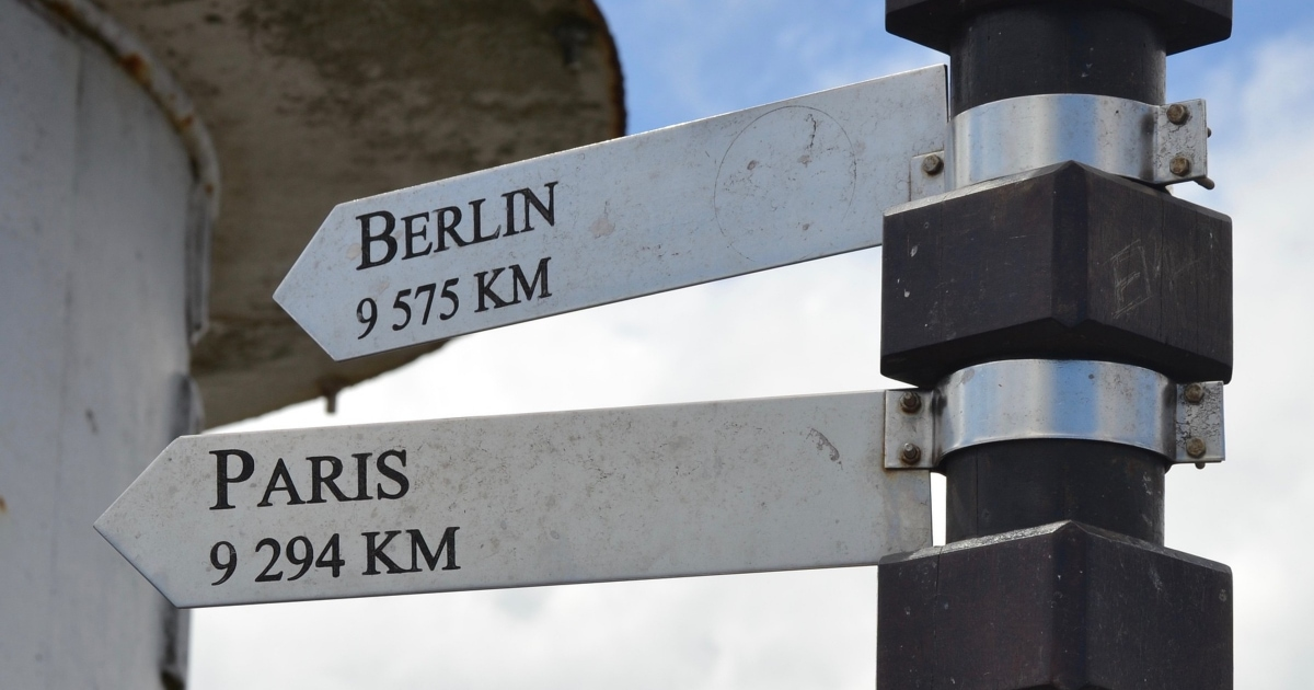 street signs pointing towards Berlin and Paris and how many KM away