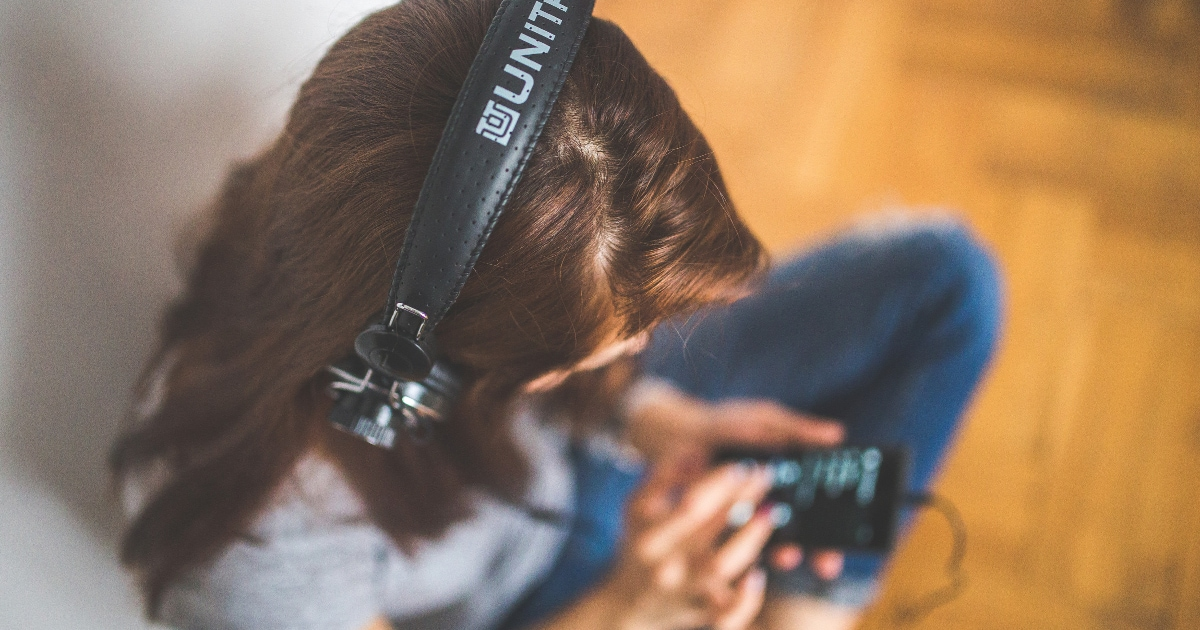 young professional woman listening to headphones