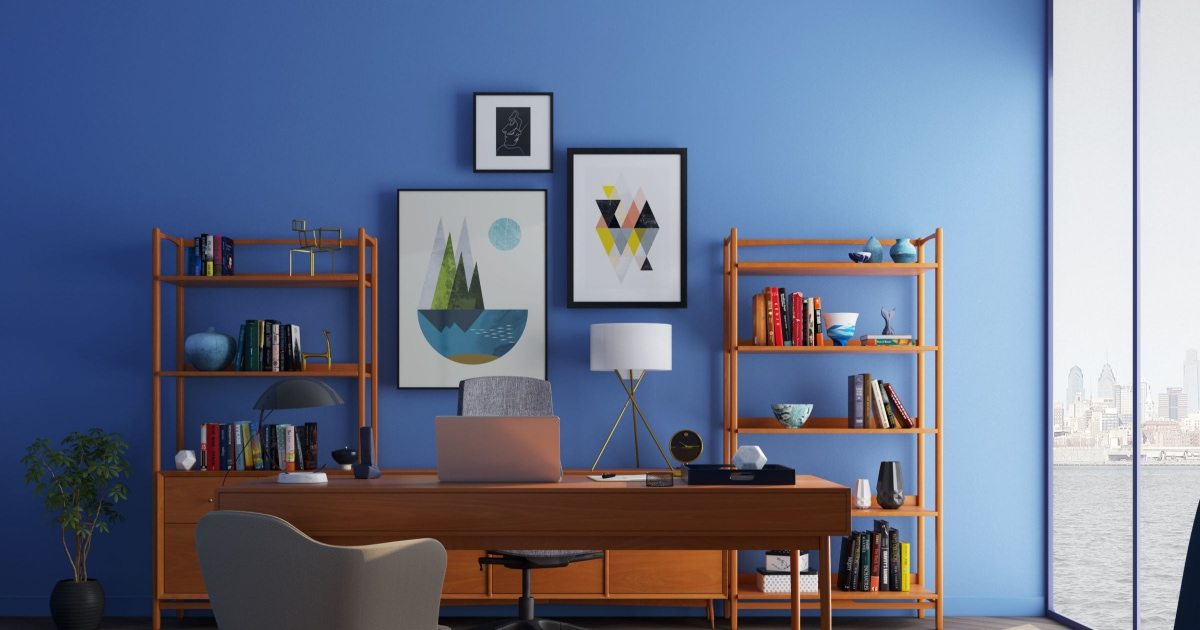view of home office with blue walls, bookshelves, desk, artwork, lighting and more