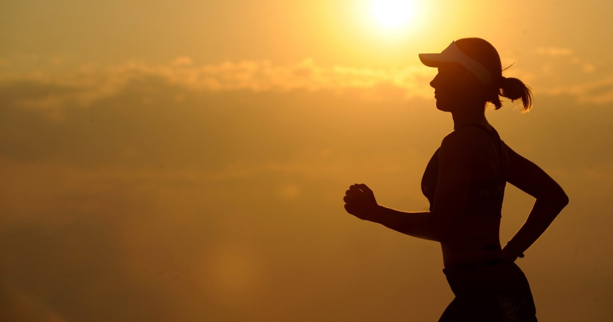 woman jogging with sunrise in background