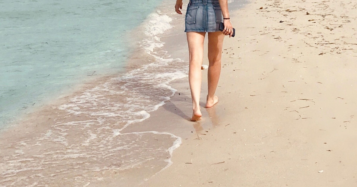 woman walks along beach with bare legs