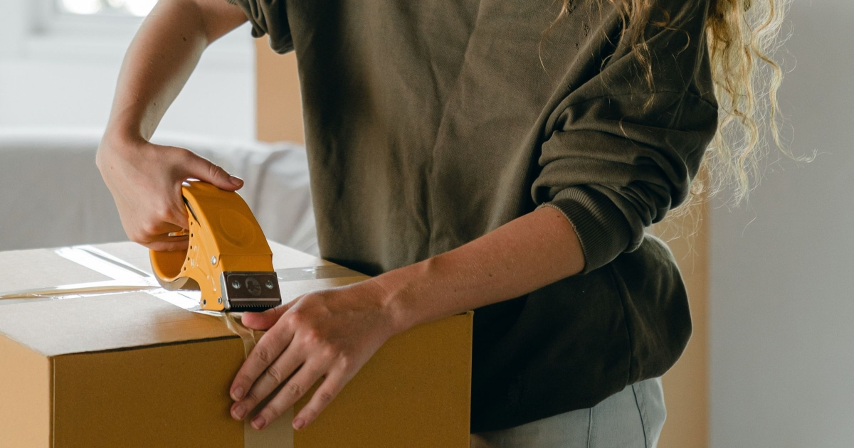 woman closing large box with packaging tape