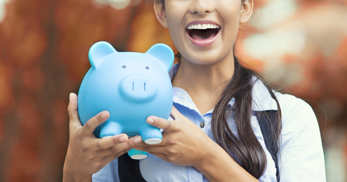 professional young woman smiling while holding a blue piggy bank